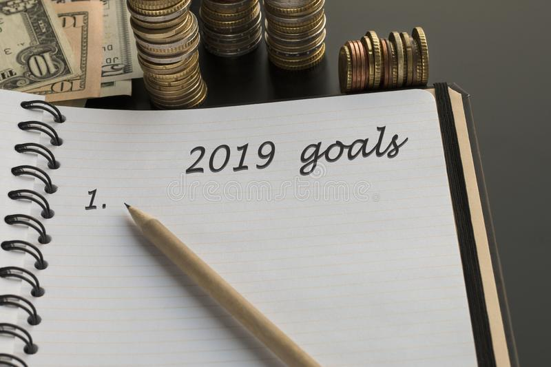 Notepad with 2019 goals text, pencil, money background stock image