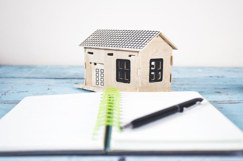 Notepad with house model. Pen on notepad with house model on table stock photos