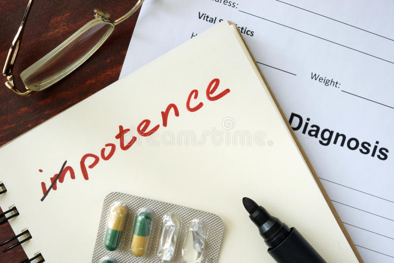 Notepad with impotence and pills. On the wooden table stock photo