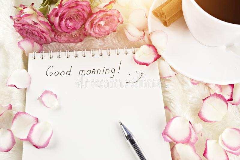 Notepad with the inscription good morning, sun, coffee, cinnamon, roses, petals, cinnamon. Notepad with the inscription good morning, sun, coffee, cinnamon royalty free stock image