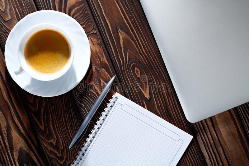 Notepad, laptop i filiżanka na drewno stole, fotografia stock