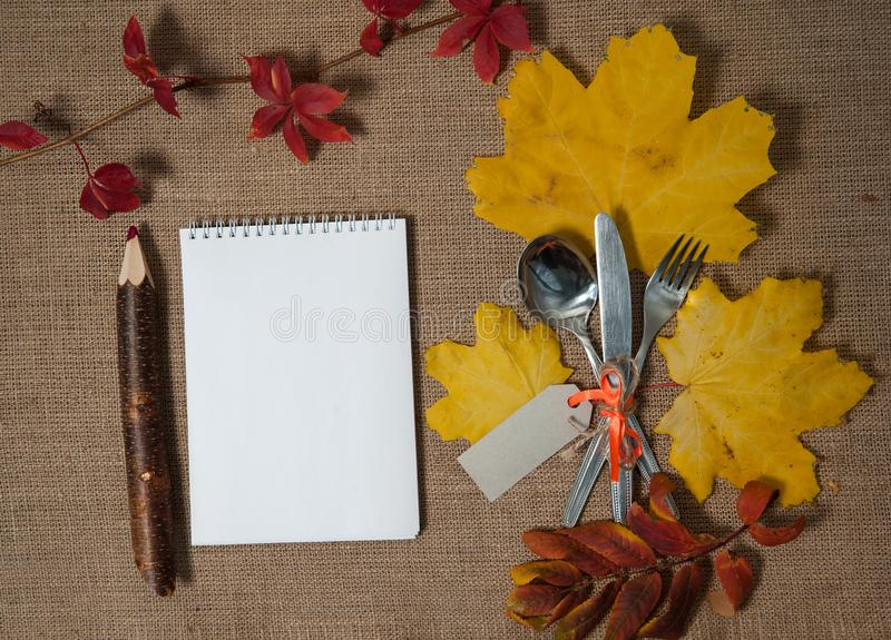 Notepad, Large pencil, spoon, fork, knife, linen napkin, autumn leaves on a textile background. Free space for your text. Composition for Thanksgiving. Notepad stock photo