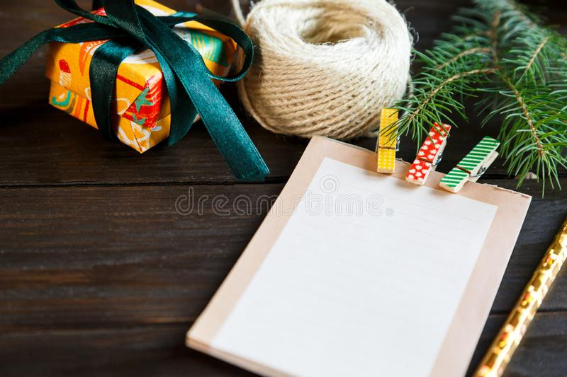 Notepad lays on the wooden background to make a list to do things or list of presents for friends and family. New year. And Christmas concept. close up royalty free stock image