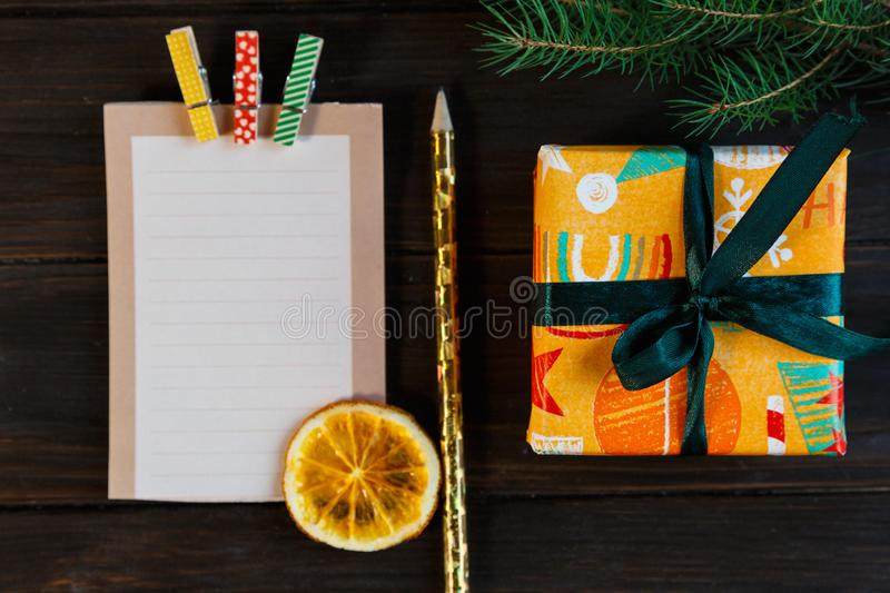 Notepad lays on the wooden background to make a list to do things or list of presents for friends and family. New year. And Christmas concept. close up stock photography