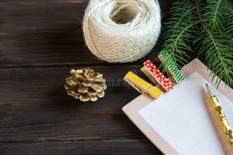 Notepad lays on the wooden background to make a list to do things, resolution or list of presents for friends and family. New year. And Christmas concept royalty free stock photo