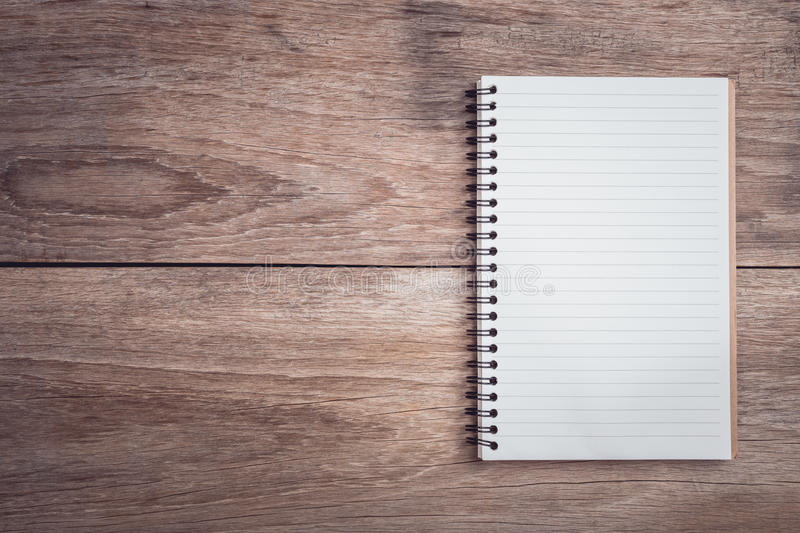 Notepad / lined paper on wooden table top view royalty free stock photography