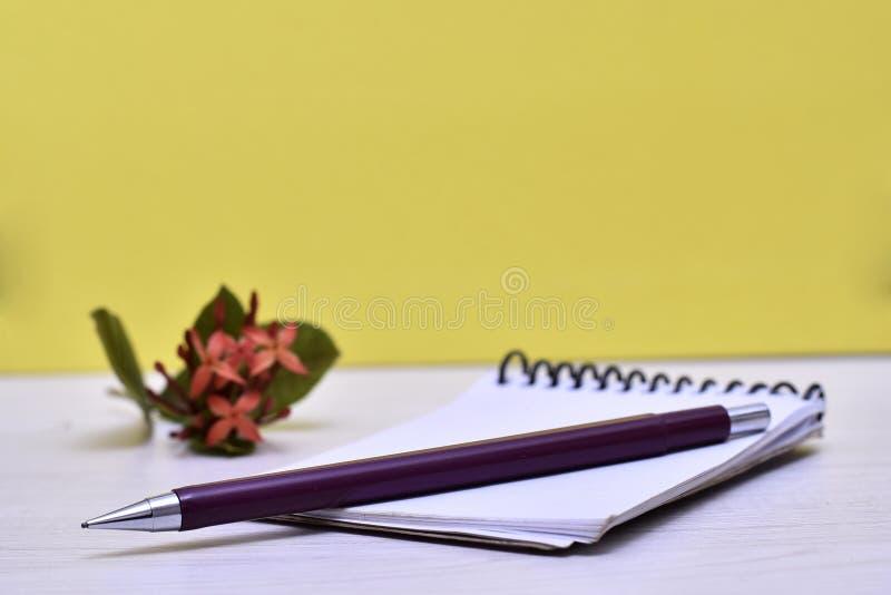 Notepad med blyertspennan, blomman och hjärta på tabellen arkivbild