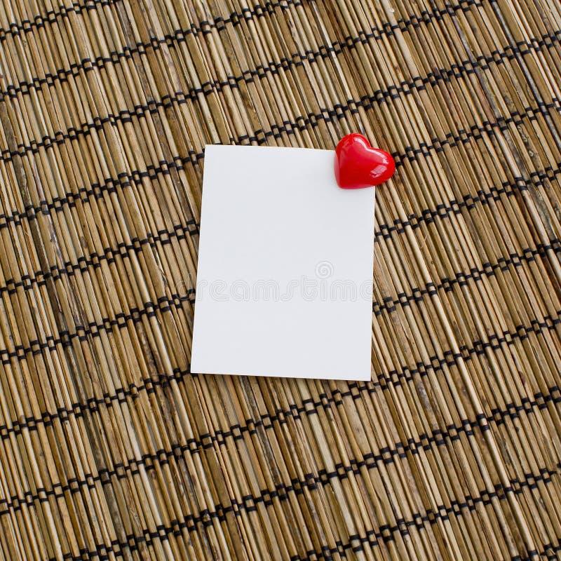 Notepad med gemet av hjärtaform med röd färg på den wood backgrouen arkivfoto