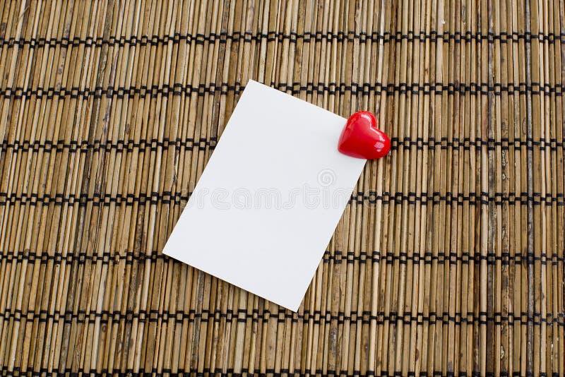Notepad med gemet av hjärtaform med röd färg på den wood backgrouen royaltyfria bilder