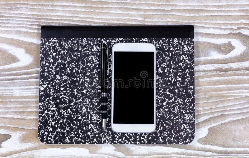Notepad med pennan och mobiltelefon överst av det gamla vita skrivbordet royaltyfri fotografi
