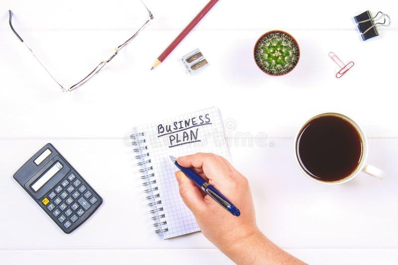 Notepad med texten: affärsplan Vit tabell med räknemaskinen, kaktus, anmärkningspapper, penna, exponeringsglas En hand rymmer en  royaltyfri bild