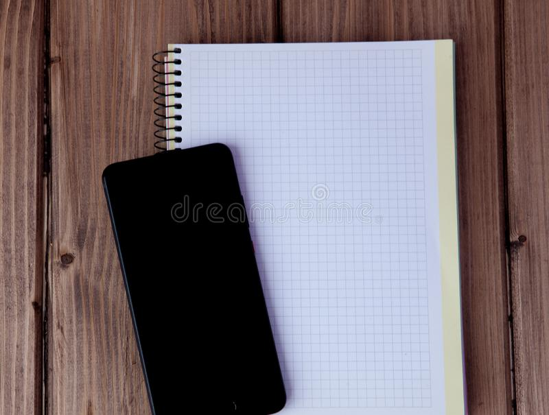 Notepad and mobile phone on wooden background. Goals for the new year. Planning and schedule concept. To do list.  stock images