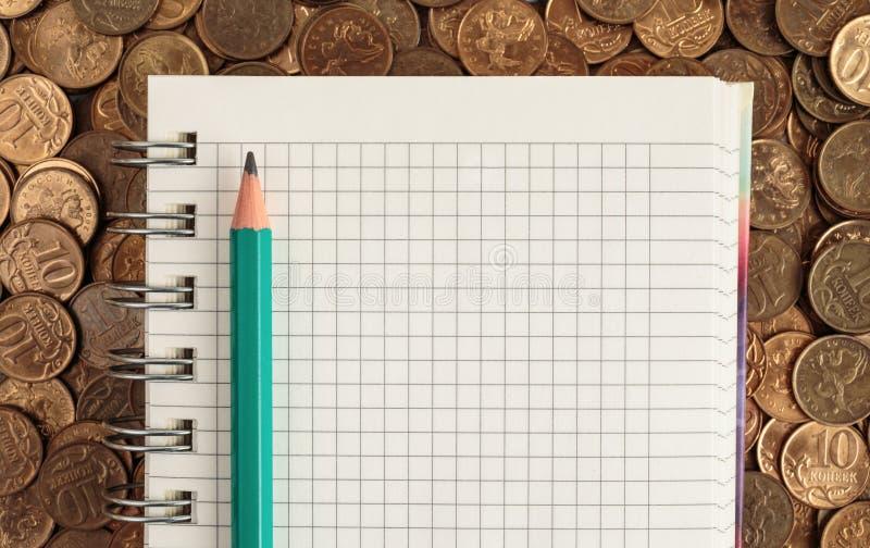 Notepad och blyertspenna på mynt fotografering för bildbyråer