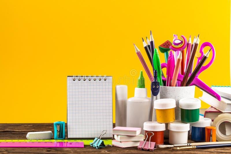 Notepad och färgrik skolabrevpapper på gul bakgrund royaltyfria bilder