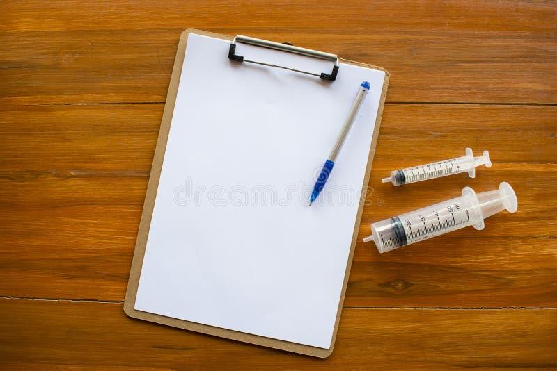 Notepad och injektionsspruta eller injektion arkivbild
