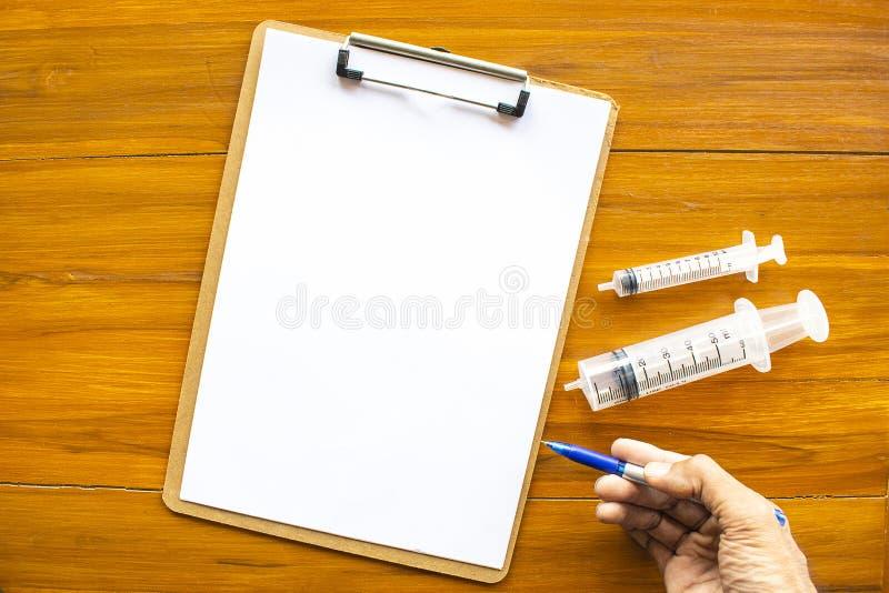Notepad och injektionsspruta eller injektion arkivfoton