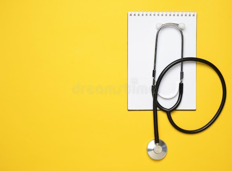 Notepad och läkarundersökningstetoskop på en gul bakgrund, minimalist trend, bästa sikt, medicinsk arbetsplats arkivfoton