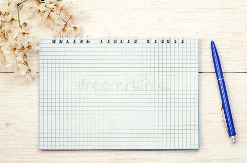 Notepad och penna med lösa vårblommor royaltyfri bild