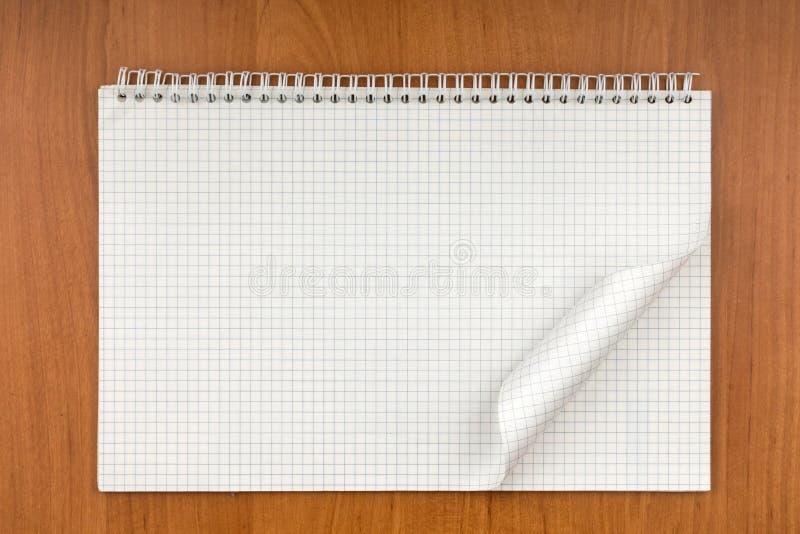 Notepad på en spiral med ett krullat ark som ligger på en tabell royaltyfri bild