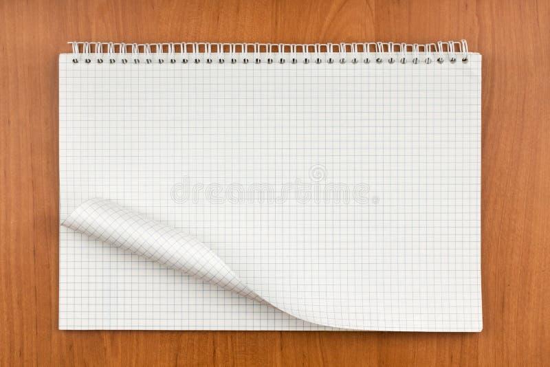 Notepad på en spiral med ett krullat ark som ligger på en tabell royaltyfri fotografi