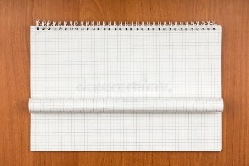 Notepad på en spiral med ett krullat ark som ligger på en tabell arkivbild