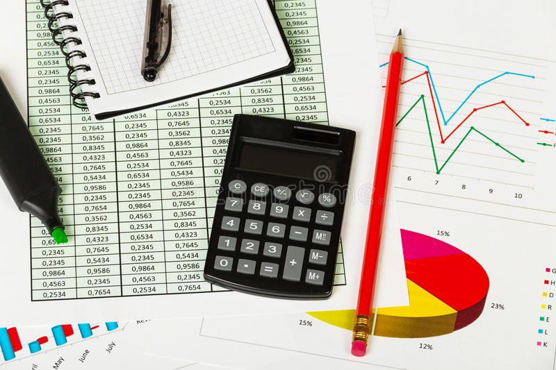 Notepad, pen, marker, pencil and calculator on background of graphs. royalty free stock photo