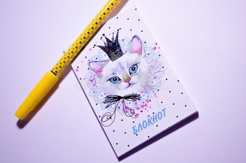 Notepad and pen. Yellow pen and notebook with a picture of a cat. Delicate notebook for notes for the girl. Place for notes. stock photos