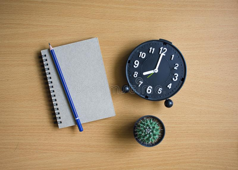 Notepad with pencil and cactus on wood board background royalty free stock image