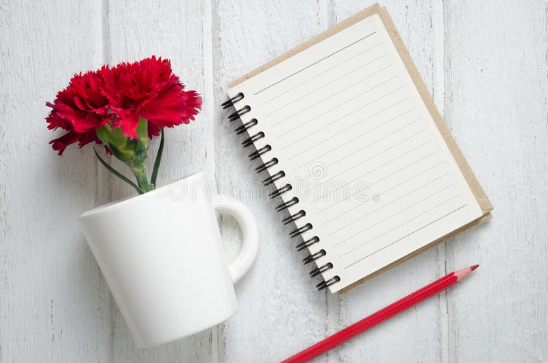 Notepad, pencil and Carnation flowers. Empty notepad, pencil and red Carnation flowers in a cup on the white wooden background, top view royalty free stock photo