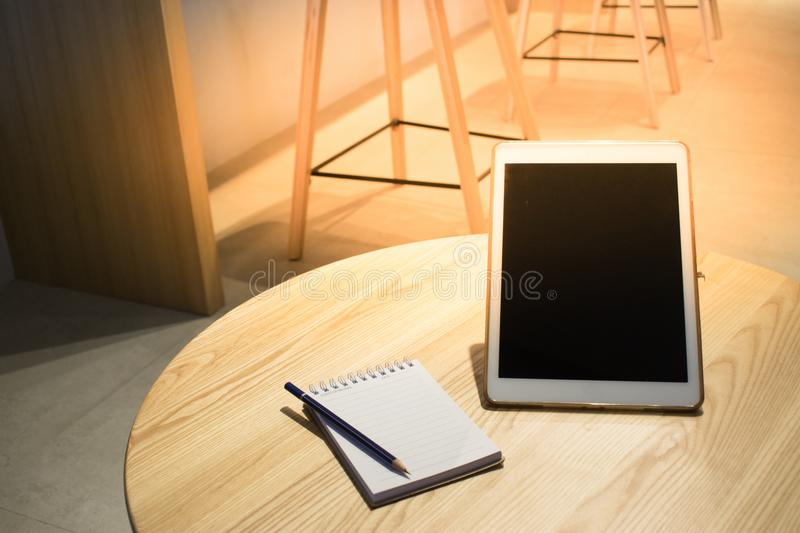 Notepad with pencil and tablet on wood board background.using wallpaper for education, business photo.Take note of the product for stock photo