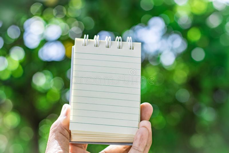 Notepad with pencil on tree blurry background in garden . using wallpaper or background for education, business photo. Take note o stock image