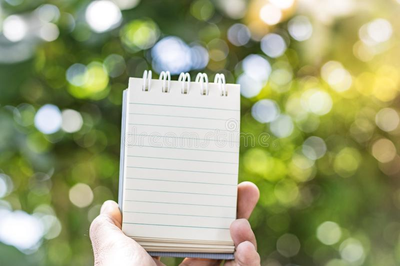 Notepad with pencil on tree blurry background in garden . using wallpaper or background for education, business photo. Take note o stock photography