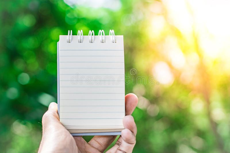 Notepad with pencil on tree blurry background in garden . using wallpaper or background for education, business photo. Take note o royalty free stock image