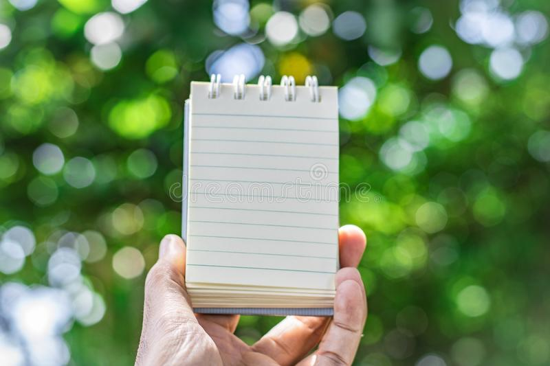 Notepad with pencil on tree blurry background in garden . using wallpaper or background for education, business photo. Take note o royalty free stock photos
