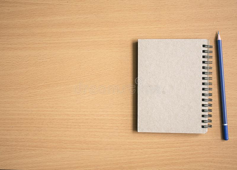Notepad with pencil on wood board1 stock photo