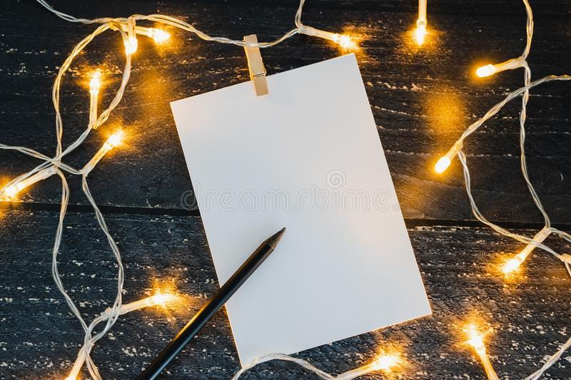 Notepad and pencil on wooden desk with copyspace to add you text surrounded by fairy lights. Concept of sharing a message stock photography