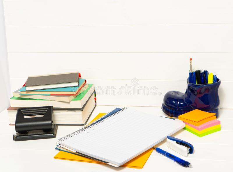 Notepad with pens and stickers. Notebook, pen, books and pencil holder in the shape of shoe on the white wooden table stock photos
