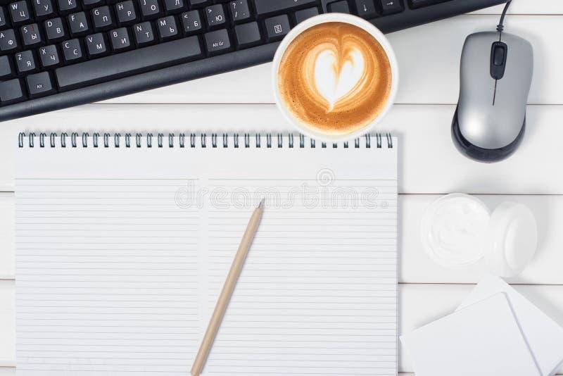 Notepad pióra filiżanki kawy kremowa klawiaturowa mysz od komputeru obrazy royalty free