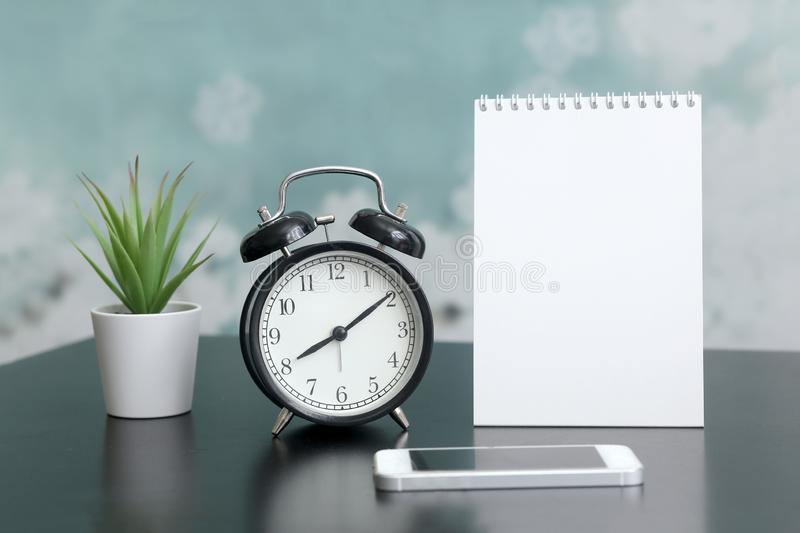 Notepad with place for text, clock, phone, home plant in a pot on the table. royalty free stock photos