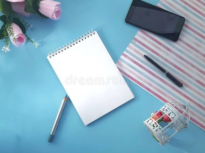 Notepad, smartphone, decorative cage and roses on light blue background. royalty free stock photos