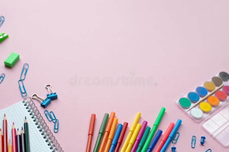Notepad with stationary objects on pink background. Place for your text. royalty free stock photography