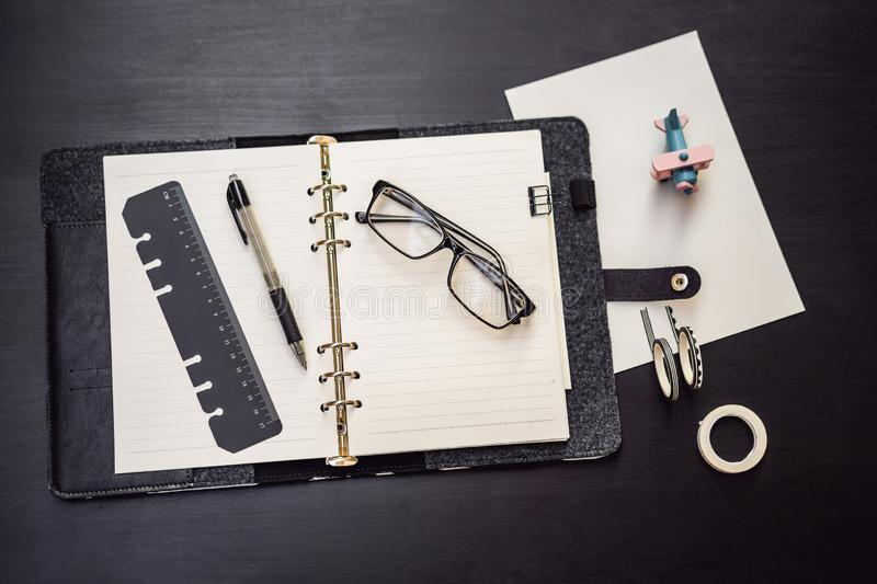 Notepad and stationery on a black background. Planner for business and study. Fans of stationery.  stock images