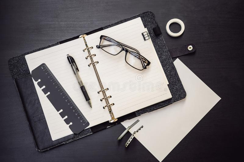 Notepad and stationery on a black background. Planner for business and study. Fans of stationery.  stock photography