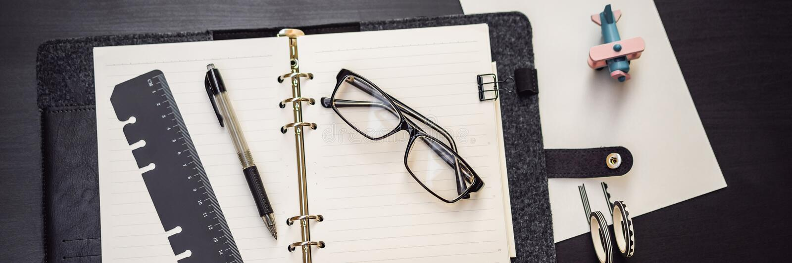 Notepad and stationery on a black background. Planner for business and study. Fans of stationery BANNER, LONG FORMAT. Notepad and stationery on a black royalty free stock photography