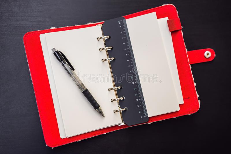 Notepad and stationery on a black background. Planner for business and study. Fans of stationery.  stock image