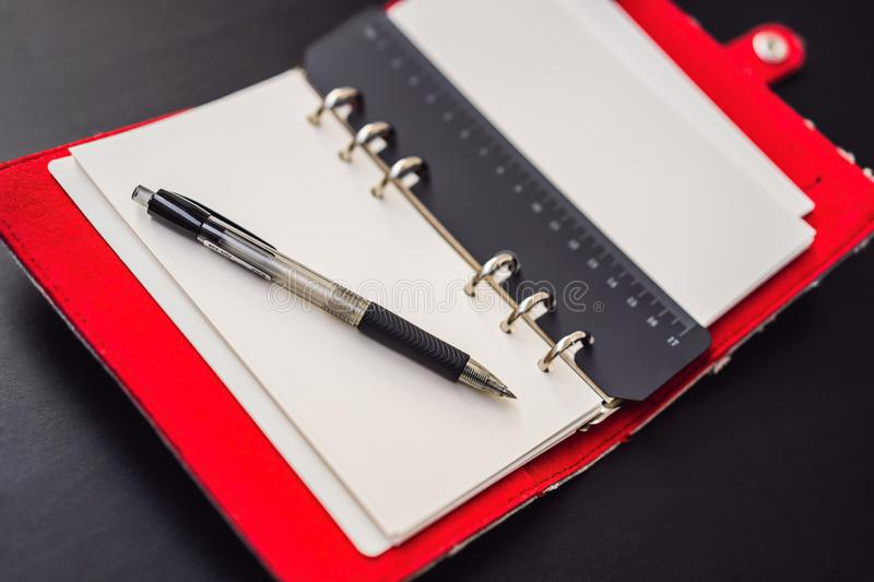 Notepad and stationery on a black background. Planner for business and study. Fans of stationery.  royalty free stock photography