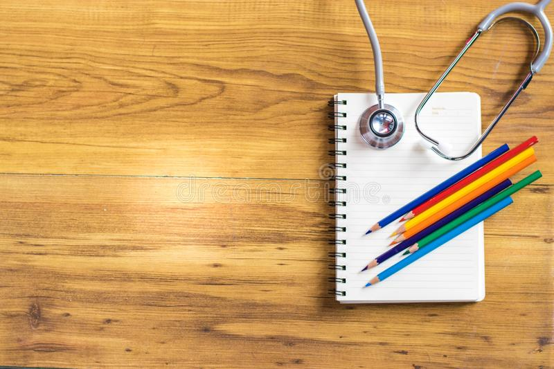 Notepad with stethoscope and pencil on wood board background.using wallpaper for education, business photo.Take note of the produc royalty free stock photos