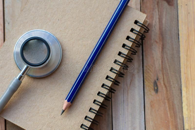 Notepad with stethoscope and pencil on wood board background.using wallpaper for education, business photo royalty free stock image