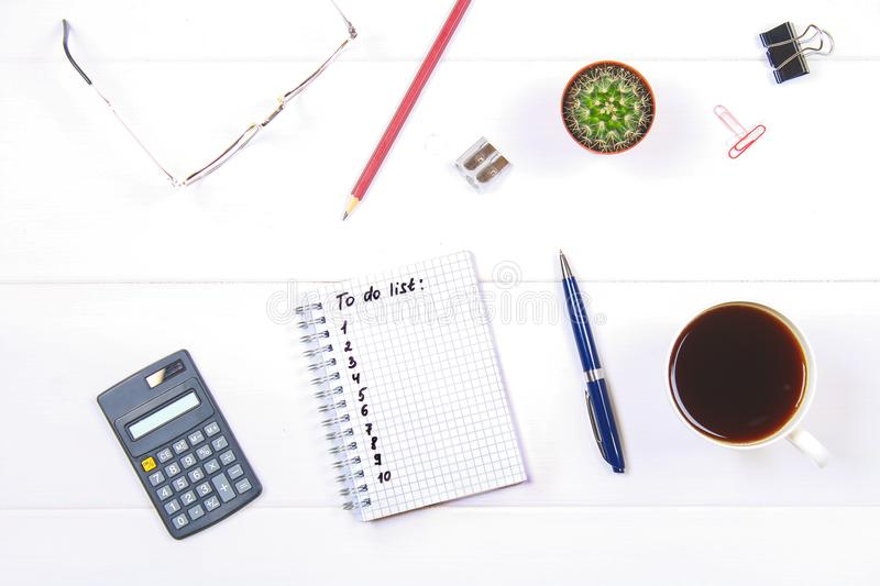 Notepad with text: To do list. White table with calculator, cactus, note paper, coffee mug, pen, glasses. stock images