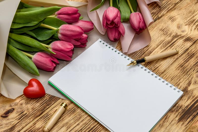 Notepad with tulip bouquet on wooden background top view.  royalty free stock image